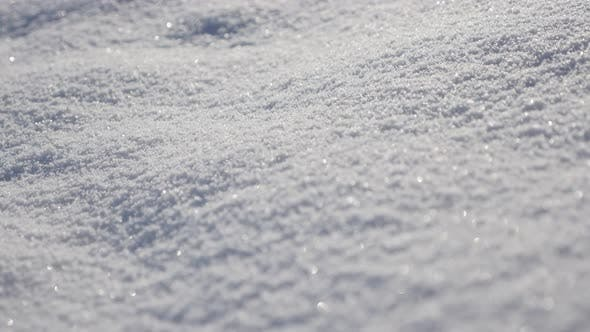 Thumbnail for Close-up of snow dunes on the early morning 4K 3840X2160 UHD tilting video - Shallow DOF of frozen c