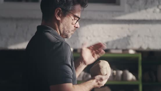 Male Artisan Slapping and Kneading Clay