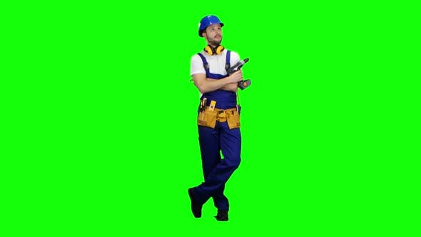 Thumbnail for Builder Holds a Drill in His Hands and Looks Around. Green Screen