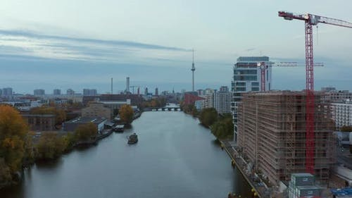 Spree River with Berlin Cityscape and Construction Site on the Riverside, Aerial Wide Angle Forward