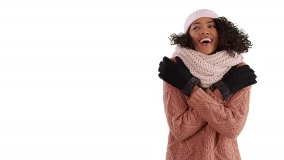 Thumbnail for Cute black female in cozy sweater trying to warm up in studio with copyspace