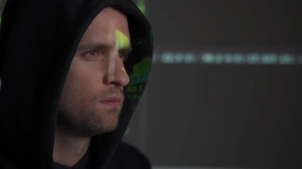 Thumbnail for Male Hacker Working on a Computer While Green Code Characters Reflect on His Face in a Dark Office