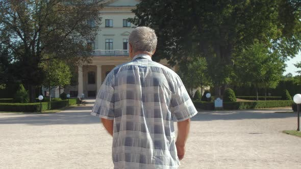 Thumbnail for Grey Haired Man Walks Against Palace and Lush Green Trees