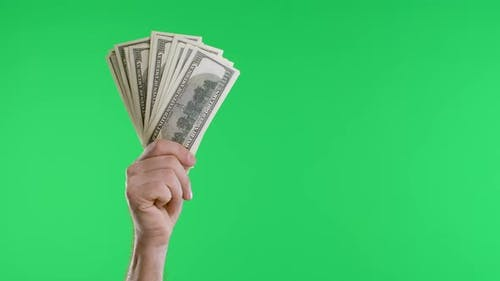 Male Hands Hold a Bundle of Dollar Bills and a Vintage Watch on a Chain Against a Green Screen