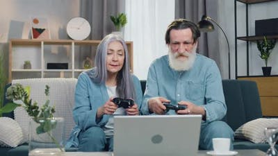 Old Couple Enjoying their Victory in Video Game and Giving High Five Each