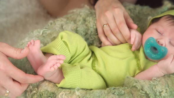 Thumbnail for Mothers Hands Holding Legs of Newborn Baby Girl
