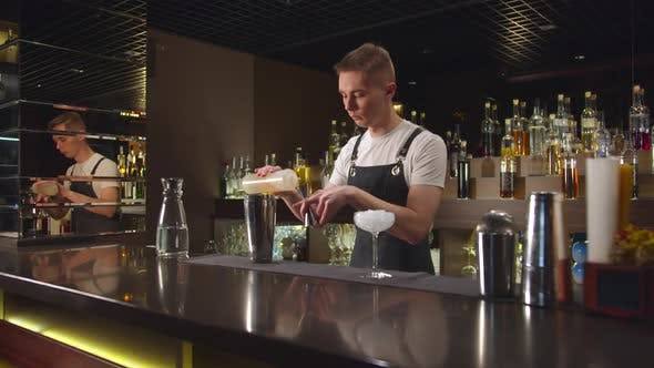 Thumbnail for Bartender Pours Alcohol in Cocktail Shaker and Mix It with Ice at the Bar