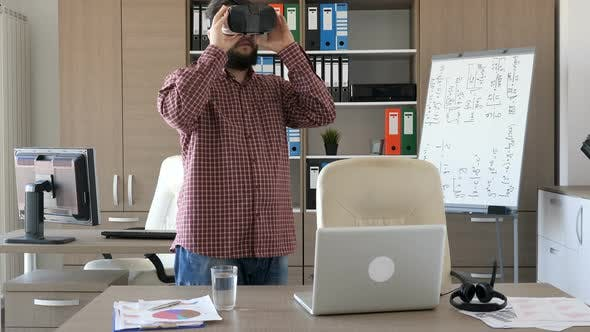 Thumbnail for Man Enters an Office and Takes a VR Headset From the Desk in Front of Him