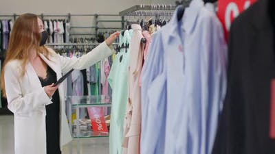 Young Female in a Clothing Store Sales Representative Takes Inventory in a Clothing Store Using the
