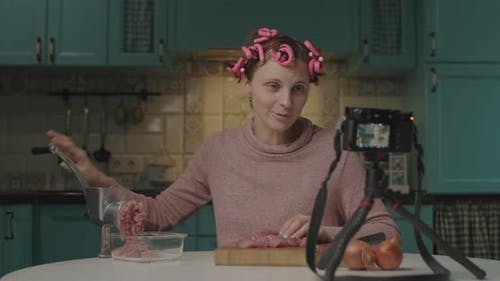 Female Food Blogger Cooking Meat in Mincer and Recording Video on Camera Sitting in the Kitchen