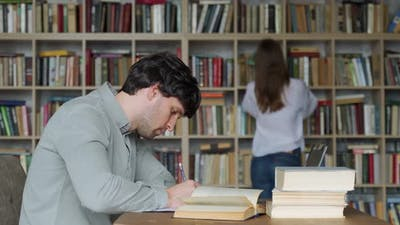 Man Student Preparing Exam and Learning Lessons in Library