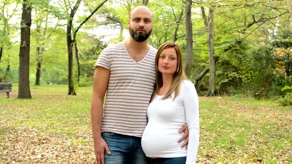 Thumbnail for Couple - Handsome Man and Young Pregnant Woman Stand Together and Look To Camera with Serious Face