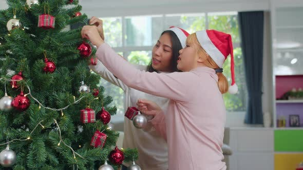 Asian women friends decorate Christmas tree at Christmas festival. Female teen happy smiling.