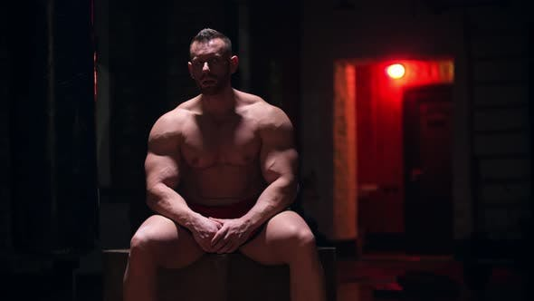 Tough Big Man Sitting in the Gym with Red Contrast Lighting