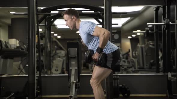 Thumbnail for Muscular man pulling heavy dumbbell at the gym.
