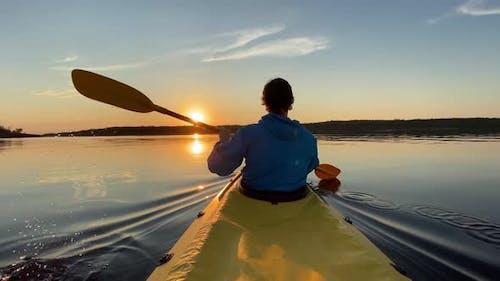 Guy Sails Kayak Along River Water Against Island at Sunset