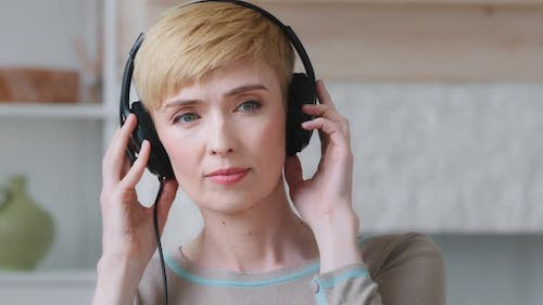 Close Up of Serene Blissful Young Woman Wear Wired Earphones Listens to Tranquil Classical Music
