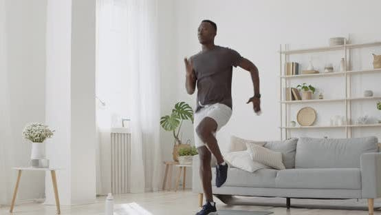 Thumbnail for Young African American Guy Energetically Jogging in Place at Home, Domestic Cardio Training
