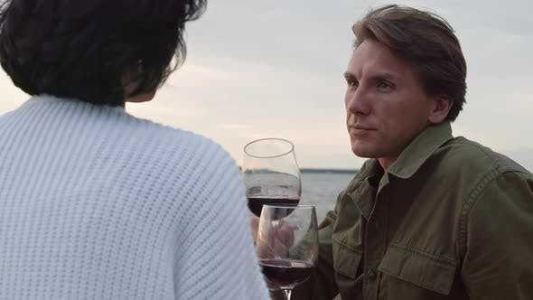 Young Man and Woman Drinking Wine on Seashore