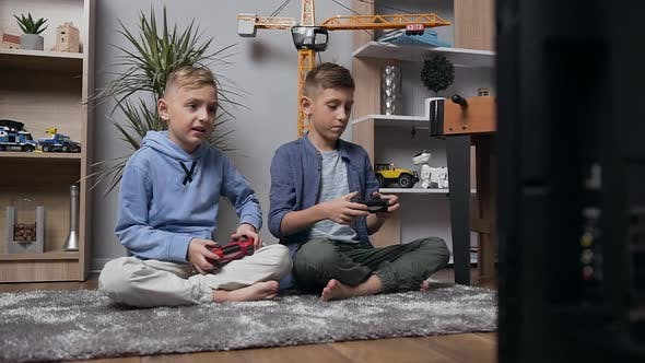 Teen Boys Sitting on the Carpet and Playing Video Game Using Joysticks