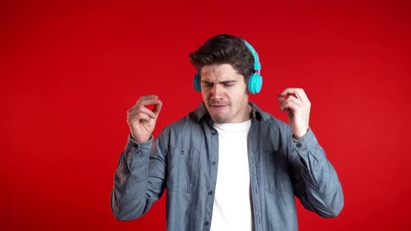 Thumbnail for Handsome Man with Headphones Dancing Isolated on Red Background