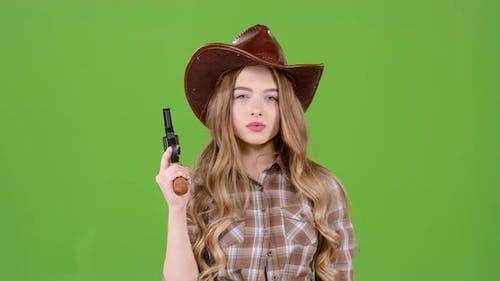 Sheriff Girl hält einen Revolver in ihren Händen und zielt auf den Bösewicht. Grüner Bildschirm