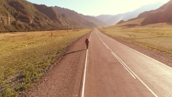 Thumbnail for Flight Over Hitchhiker Tourist Walking on Asphalt Road. Huge Rural Valley at Summer Day. Backpack