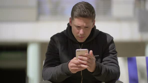 Thumbnail for Focused Man in Hoodie Using Smartphone Outdoor