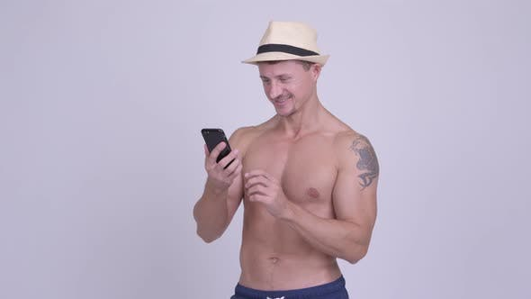 Thumbnail for Happy Muscular Bearded Tourist Man Using Phone and Taking Selfie Shirtless