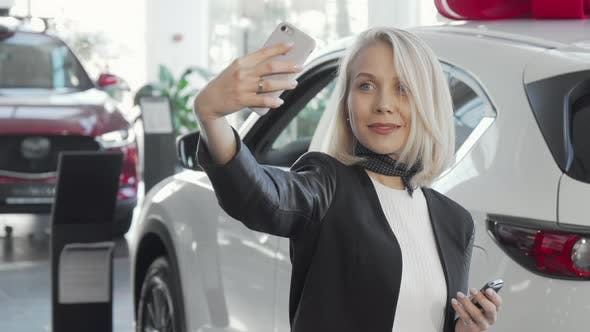 Thumbnail for Happy Woman Taking Selfies with Keys To Her New Car at the Dealership