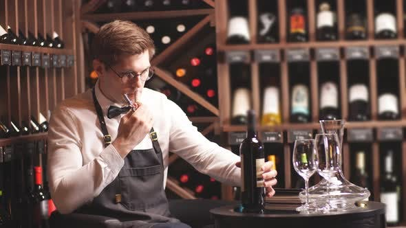 Thumbnail for Elegant Young Sommelier with Bow Tie Uncorking Bottle of Wine in Wine Boutique.