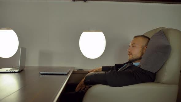 Tired Business People Sleeping on Board Airplane