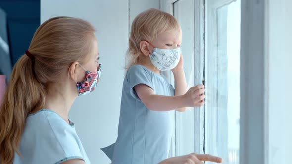 Thumbnail for Mom with a Small Child in a Mask Are Sitting at the Window During Quarantine