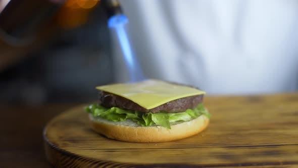 Chef Melts Cheese with Help of Gas Burner on the Cutlet in Process of Making Burger in Restaurant