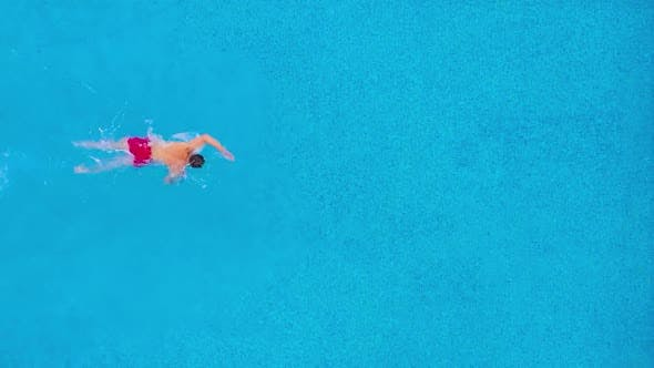 Thumbnail for Aerial View of Man in Red Shorts Swims in the Pool. Slow Motion