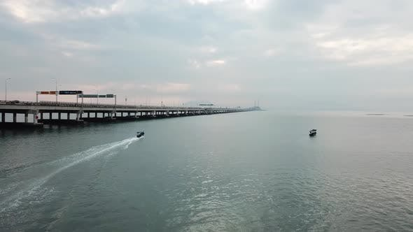 Fisherman boat move toward Penang Bridge.