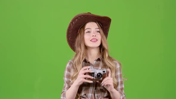 Thumbnail for Girl in a Cowboy Hat Walks and Photographs Beautiful Buildings. Green Screen
