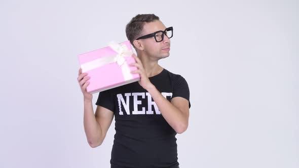 Thumbnail for Studio Shot of Happy Nerd Man Shaking Gift Box