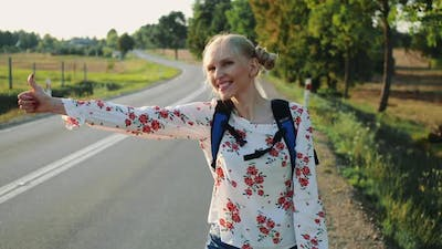 Traveler Woman Hitchhiking on a Sunny Road and Walking