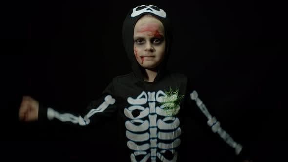 Halloween Angry Girl mit Blut Make-up auf Gesicht. Kind als beängstigend gekleidet, Tanzen, Gesichter machen
