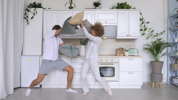 Thumbnail for Funny Couple Fighting With Pillows In Kitchen