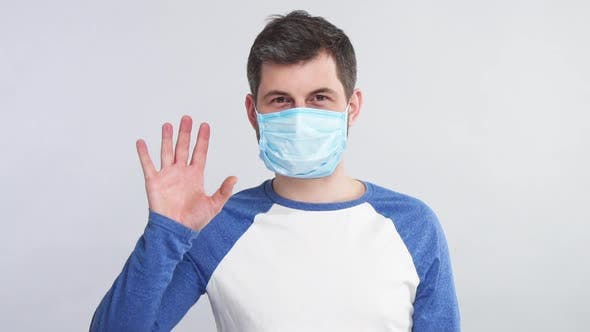 Thumbnail for Sick Man in Respiratory Sterile Mask Showing Stop Sign with His Arm To the Camera