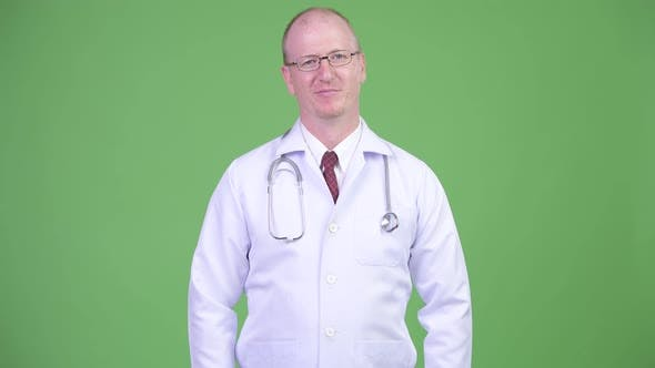Thumbnail for Happy Mature Bald Man Doctor Wearing Eyeglasses Against Green Background