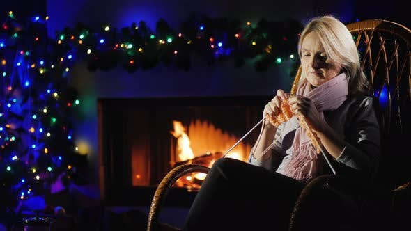 Thumbnail for Evening By the Fireplace Before Christmas - a Woman Knits Warm Clothes