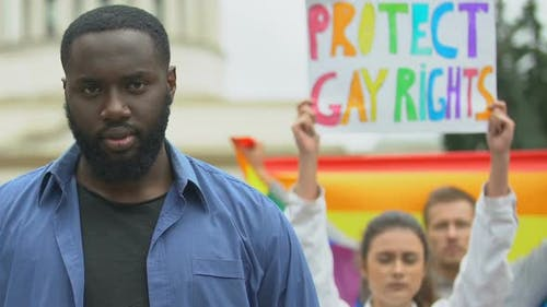 Black Man Raising Rainbow Heart Together With Protesters for LGBT Rights, Rally
