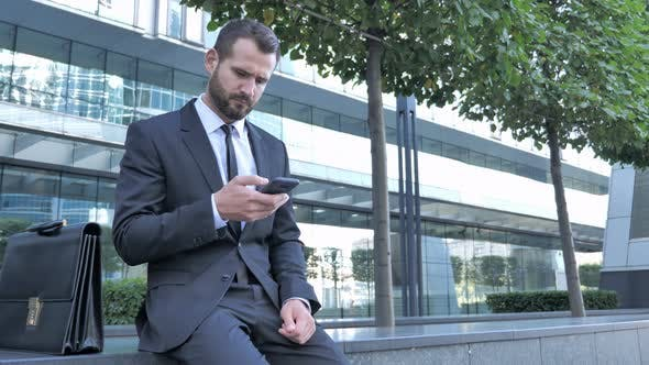 Cover Image for Businessman Typing Message on Smartphone