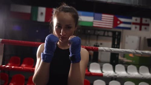 Closeup Shot of Confident Female Fighter with Wrapped Hands Looking at Camera While Posing in Gym