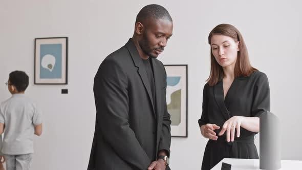 Couple Discussing Art Exhibit in Museum