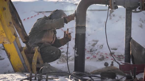 Thumbnail for Worker Produces Pipe Welding on the Street. In Winter, at Low Temperatures
