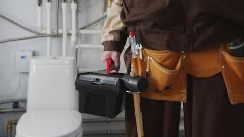 Unrecognizable Plumber with Tool Belt and Toolbox